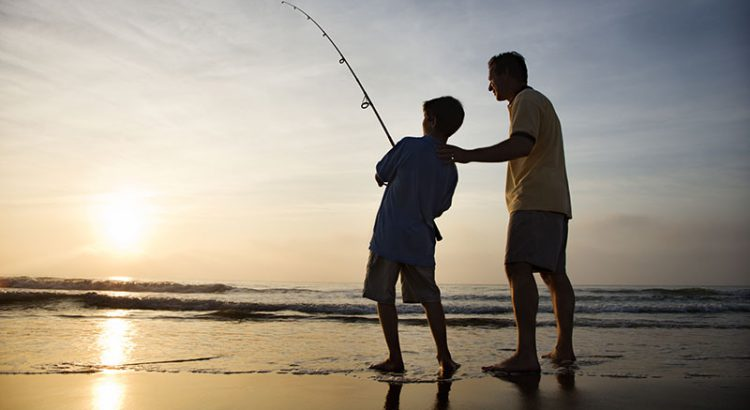 Father and son fishing in the ocean surfing at sunset