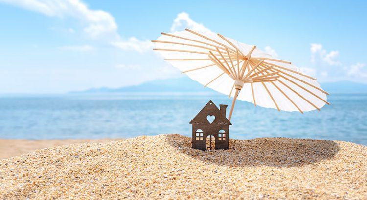 Paper house with umbrella on the beach